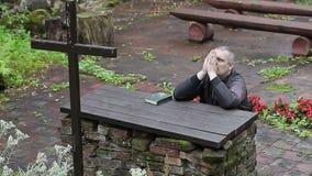 De mens met Bijbel en rozentuin bidt het knielen bij het altaar stock video