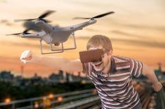De mens met 3D virtuele werkelijkheidsglazen controleert een vliegende hommel Royalty-vrije Stock Foto