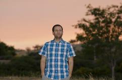 De mens met dient zijn zakken bij zonsondergang in weg kijkend aan het recht Stock Fotografie