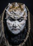 De mens met doornen of wratten, gezicht wordt behandeld die met schittert Demon met gouden kap op zwarte achtergrond Hogere mens  stock afbeelding