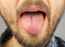 De mens met een baard opende zijn mond en plakte uit zijn tong Royalty-vrije Stock Afbeelding