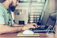 De mens met een baard werkt bij de computer, aan achtergrond twee vloeren van flats Stock Foto's