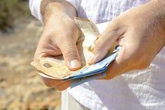 De mens met een geld in zijn handen begint te tellen Stock Afbeelding