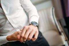 De mens met een horloge knoopt wit overhemd dicht royalty-vrije stock afbeeldingen