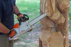 De mens met een kettingzaag creeert een beeldhouwwerk van hout wordt gemaakt dat stock afbeeldingen