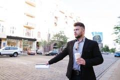 De mens met een kop van koffie in zijn handen bevindt zich door de weg en haalt een taxi stock foto's