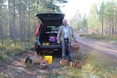 De mens met een mand van eekhoorntjesbroden schiet in het bos en een auto op achtergrond als paddestoelen uit de grond Royalty-vrije Stock Foto