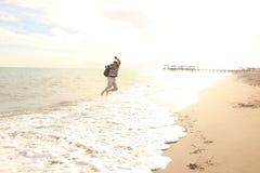 De mens met een omhoog rugzak op de overzeese sprongen, is een golf gekomen stock foto