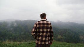 De mens met een snor en een baard op de berg kijkt rond en rookt stock video