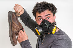 De mens met gasmasker houdt stinky schoen Stock Afbeeldingen