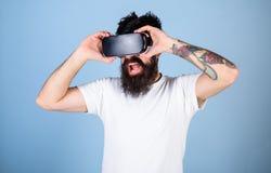 De mens met geamuseerd kijkt en opent mond genietend van 3D ervaring Gebaarde mens die met tatoegering op video 360 in VR-bescher stock foto