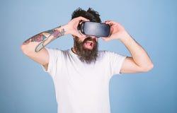 De mens met geamuseerd kijkt en opent mond genietend van 3D ervaring Gebaarde mens die met tatoegering op video 360 in VR-bescher royalty-vrije stock foto