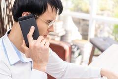 De mens met glazen die zwarte mobiele omhoog gesloten telefoon met behulp van schoot, bri royalty-vrije stock foto's