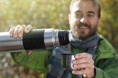 De mens met glimlach giet een hete drank - thee of koffie binnen van thermosflessen stock foto