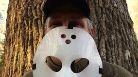 De mens met Halloween-masker behandelt zijn gezicht en vampiertanden stock footage