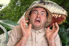 De mens met helm loopt vanaf enge dinosaurus stock afbeeldingen
