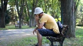 De mens met hoed en zonnebril spreekt neer door telefoonzitting op parkbank De mens spreekt met telefoon terwijl het ontspannen i stock footage