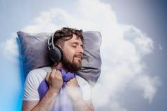 De mens met hoofdtelefoons, klinkt in slaap royalty-vrije stock afbeelding