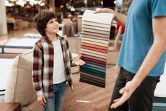 De mens met jonge jongen kiest kleur op kleurenpalet Het selecteren van kleur van matras op de gids van het kleurenpalet Stock Fotografie