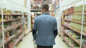 De mens met karretje gaat onder planken met goederen in supermarkt, achtereindmening, steadicam schot stock video