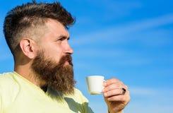 De mens met lange baard geniet van koffie Koffie gastronomisch concept De mens met baard en snor op strikt gezicht drinkt blauwe  stock fotografie