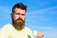 De mens met lange baard geniet van koffie Koffie gastronomisch concept De gebaarde mens met espressomok, drinkt koffie Mens met b stock foto