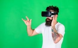 De mens met lange baard in VR-beschermende brillen 3D letten op toont Brutale gebaarde mens die van geregistreerd rotsoverleg gen Royalty-vrije Stock Foto's