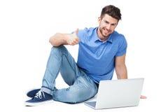 De mens met laptop het tonen beduimelt omhoog stock afbeelding
