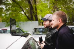 De mens met laptop in parkeerterrein in werf dichtbij auto doet manipulaties met cybersysteem, concept Stock Afbeeldingen