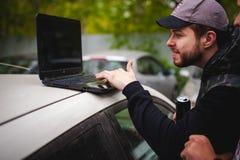 De mens met laptop in parkeerterrein in werf dichtbij auto doet manipulaties met cybersysteem, concept Stock Afbeelding