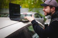 De mens met laptop in parkeerterrein in werf dichtbij auto doet manipulaties met cybersysteem, concept Royalty-vrije Stock Afbeelding