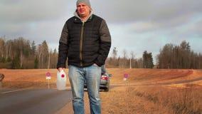 De mens met leeg kan wachtend op hulp dichtbij auto op de weg stock videobeelden