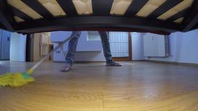 De mens met leren riemen wast de vloer onder het bed stock footage