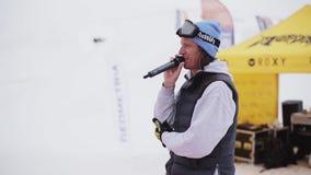 De mens met microfoon zegt onder snowboarders en skiërs bij de skitoevlucht sneeuw stock video