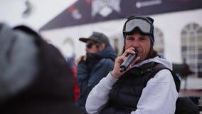 De mens met microfoon zegt onder snowboarders en skiërs bij de skitoevlucht Sport stock video