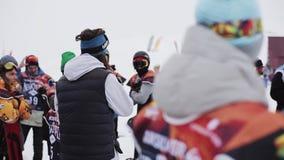 De mens met microfoon zegt onder snowboarders en skiërs bij de skitoevlucht wedstrijd stock videobeelden