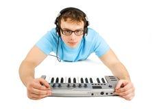 De mens met Midi toetsenbord en hoofdtelefoons ligt Royalty-vrije Stock Afbeeldingen