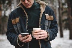 De mens met mobiele telefoon drinkt koffie openlucht Stock Afbeelding