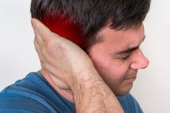 De mens met oorpijn houdt zijn pijnlijk oor stock foto