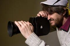 De mens met retro camera schiet de filmspanning Stock Fotografie