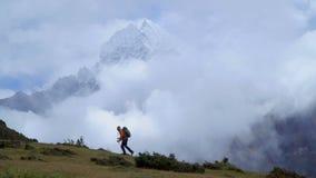 De mens met rugzak beklimt de berghelling in het Himalayagebergte stock video