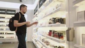 De mens met rugzak probeert parfums in een opslagzaal, zijaanzicht stock videobeelden