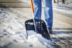 De mens met sneeuwschop maakt schoon Royalty-vrije Stock Foto's