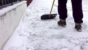 De mens met sneeuwschop maakt stoepen in de winter schoon stock videobeelden