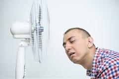 De mens met stoppelveld op zijn gezicht lijdt aan de hitte en het proberen om weg dichtbij de ventilator te koelen stock afbeeldingen
