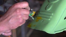 De mens met tatoegeringen kleurt de details van de motorfiets in de garage stock footage