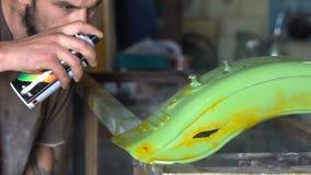 De mens met tatoegeringen kleurt de details van de motorfiets in de garage stock videobeelden
