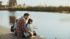 De mens met twee kinderen zit en spreekt op rivierpijler Enige vader die zijn familie bouwen Het ter sprake brengen van nieuwe ge stock footage