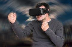 De mens met virtuele werkelijkheidsbeschermende brillen speelt 3D spelen Stock Afbeeldingen