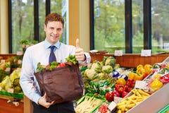 De mens met winkelende zakholding beduimelt omhoog Royalty-vrije Stock Foto